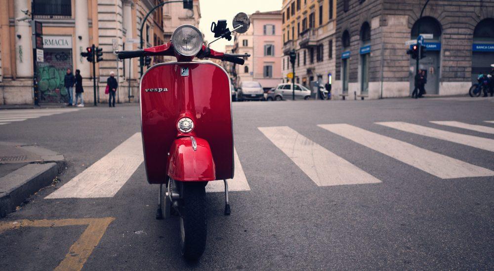 Vespa rossa vintage in una strada italiana